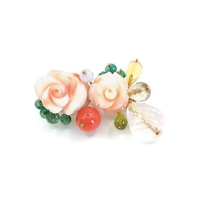 花束で胸元を飾るバラ珊瑚のブローチ